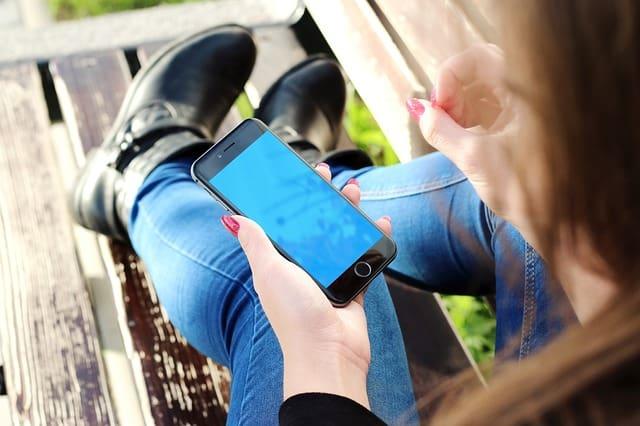 Girl typing in iPhone passcode